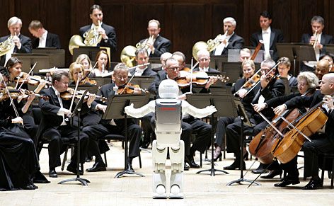 Honda's ASIMO robot conducts the Detroit Symphony Orchestra as it performs Impossible Dream during a concert on Tuesday. Honda Motor designed ASIMO, which stands for Advanced Step in Innovative Mobility.ASIMO can't respond to the players, but mimicked the actions of a conductor who was videotaped beforehand.