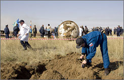 Ground crew members check levels of radiation next to the Soyuz capsule after it landed in northern Kazakhstan. The botched landing of the Russian capsule last month  was caused by the failure of an equipment module to separate from the capsule on time