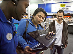 Narges Anbardar, middle, and Mani Jalilian, far right, shop for a laptop computer Thursday in Watertown, Mass., as Best Buy associate Greg Xavier tries to help them make their choice.