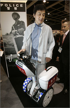 Hong Kong movie star Jackie Chan demonstrates his Segway scooter at the security fair in Hong Kong. Chan says his Chinese dealership for the Segway scooter is doing well, but Segway's owners are keeping his costs up out of piracy fears.