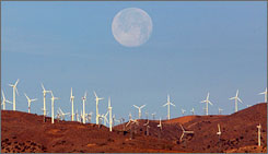 The full moon sets behind a wind farm in the Mojave Desert in California.    To our eyes, the moon seems bigger when it's near the horizon.