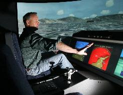 Electronics Technician Aaron Opperman demonstrates a flight simulator that his team is working on, Monday, May 19, 2007, at Rockwell Collins in Cedar Rapids, Iowa. Fewer college students are pursuing computer-related degrees at a time when demand is increasing and thousands of baby boomers are retiring from technical jobs.
