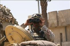 An Iraqi soldier looks through his binoculars as several hundred soldiers fans out onto the streets of Sadr City district in eastern Baghdad. The neural binoculars in development could help soldiers quickly identify threats in the field.