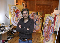 Nasser Azam poses with his paintings in his studio in Londonr.  Azam was among the three British artists who took part in a performance piece aboard a Russian aircraft used for cosmonaut training.
