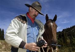 Idaho Rancher Paul Nettleton checks his Iridium satellite phone  near his ranch in Silver City, Idaho. Nettleton was one of seven rural Owyhee County cattlemen to receive a satellite phone from the Bureau of Land Management in order to help alert land managers of wildfires in rural portions of the state.