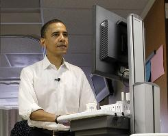 Democratic presidential candidate Barack Obama pushes a portable computer as he follows a nurse at a June appearance at a St. Louis hospital.