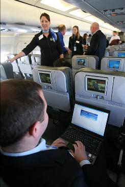 Yahoo executive Brad Garlinghouse demonstrates capabilities of a laptop at a media event aboard a JetBlue plane equipped with a wireless network.