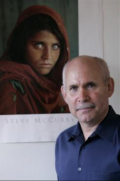 Photographer Steve McCurry poses for a portrait with a poster of  his iconic photo of the Afghan girl in New York.  McCurry, who shot the picture with Kodachrome, is turning to digital cameras as the technology gap closes.