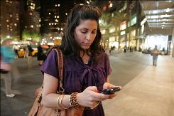 Erica Domesek checks messages on her BlackBerry, after a after-hours party at The Time Warner Center, in New York City. Domesek is a self styled workaholic whose day starts early and goes late  into the night. A Pew study found  46% of American workers said technology increases the demands that they work more hours.