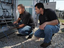 Sprint workers Roger Ho, left, and Paul Grunwald examine installations at a WiMax transmission tower in Ellicott City, Md., in suburban Baltimore.
