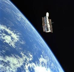 The Hubble Space Telescope (HST) floats gracefully above the blue Earth after release from Discovery's robot arm after a successful STS-103 servicing mission in December 1999.