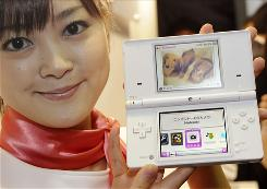 A model shows a Nintendo DSi, the revamped version of Nintendo's hit DS portable machine, during a press event in Tokyo. The DSi will come with a digital camera that will allow players to mix images, scribble on photos and create new faces. The Nintendo DSi will go on sale in Japan on Nov. 1 and will be available overseas next year.