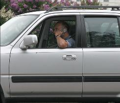 A new service promises to cut back on cellphone calls while driving.  This gentleman was photographed at a stop light on Third St. N.W. near the Capitol in Washington, D.C..