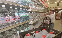 Joseph Brown stocks bottled water on shelves of a Washington grocery store Wednesday July 10, 1996. All last week Washingtonians were unsure about whether to drink the water, boiling orders were issued and then rescinded, and finally water officials poured more chlorine into the system. The reason: signs the city's water pipes were full of bacteria. (AP Photo/Wilfredo Lee) ORG XMIT: WX123