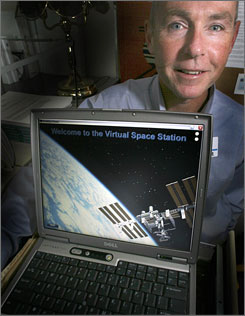 "Dartmouth psychologist Dr. Mark Hegel poses in his office with his laptop in Lebanon, N.H. Hegel is working on a computer program, ""The Virtual Space Station,"" that will guide astronauts through treatment for depression and other problems while in space."