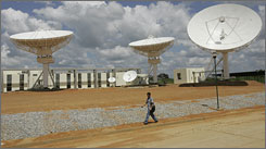 A man walks past a satellite center station in El Sombrero, Venezuela.