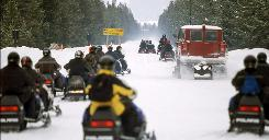 This photo provided by the National Park Service shows snowmobile traffic passing through the west entrance into Yellowstone National Park during the busy President's Day holiday weekend in Feb. 2000, in Montana.