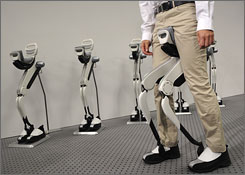 A researcher shows off Honda Motor Co.'s experimental walking assist device with bodyweight support system on a slope as the device during an unveiling in Tokyo.