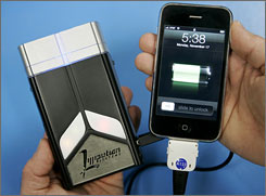 A USB mobile power system, left, produced by Lilliputian Systems, Inc., charges an iPhone, right, at the manufacturers facilities in Wilmington, Mass.