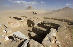 Two camel riders pass by the excavations at the Saqqara burial site of the rulers of ancient Memphis, about 12 miles, 19 kilometers south of Cairo.