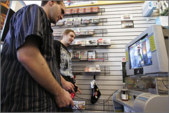 Customers play a game at a GameStop store in Redwood City, Calif.