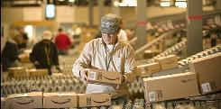 An Amazon.com employee grabs boxes off the conveyor belt to load in a truck at their Fernley, Nev., warehouse.