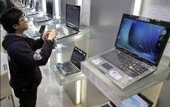 A man plays with a laptop at a computer store in Taipei.