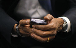 In this July 7, 2008, photo, Barack Obama checks his BlackBerry in St. Louis, Mo., prior to a conference call with supporters gathered at a campaign rally in Charlotte