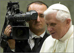 A CTV (Central Television Vatican) cameraman stands near Pope Benedict XVI during a weekly general audience in the Vatican last August. The pope on Friday became one of the oldest people to have his own YouTube channel.