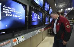 Doug Pongrazc checks out a large screen television while shopping at a Best Buy store in Elk Grove,  Calif., Thursday, Jan. 22, 2009. While flat-screen TVs have become the top sellers, they are also major energy hogs.  The California Energy Commission is expected to to adopt rules this summer requiring  retailers by 2011 to sell only TVs that meet guidelines by the federal Energy Star program.