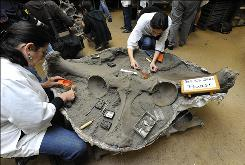 "Volunteers Meganne Macias (R) and Dixie Swift (L) work on the giant pelvis of ""Zed,"" a Colombian mammoth fossil discovered 80 percent complete, in the laboratory at the Page Museum at the La Brea Tar Pits in Los Angeles on February 18, 2009.  The ice age mammoth weighed approximately 10,000 pounds, was stood about 10 feet tall and is between 10,000 and 40,000 years old. The site was initially uncovered two years ago by workers digging a nearby underground garage.  The find, named ""Project 23,"" also includes the largest known cache of fossils, including smaller fossils of tree trunks, turtles, snails, clams, millipedes, fish, gophers and even mats of oak leaves from the last Ice Age."