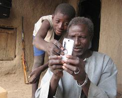 In this Oct. 19, 2007 file photo, Alaburu Maiga, right, tries to use the camera on his cell phone with the help of an unidentified boy in the village of Gono, Mali. Six in ten people around the world now have cell phone subscriptions, signaling that mobiles are the communications technology of choice particularly in poor countries, according to a U.N. report published Monday.