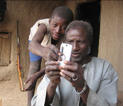 Alaburu Maiga, right, tries to use the camera on his cellphone with the help of an unidentified boy in the village of Gono, Mali, last year. Six in 10 people around the world now have cellphone subscriptions, signaling that mobiles are the communications technology of choice particularly in poor countries, according to a U.N. report published Monday