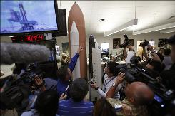 NASA spokesman Steve Roy points to the location of a hydrogen leak on a space shuttle model as the media crowds around after a delay in the launch of the space shuttle Discovery was announced. NASA delayed the launch on Wednesday of the space shuttle Discovery for at least a day because a fuel leak was discovered during launch preparations.