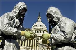With the U.S. Capitol in the background, members of an the U.S. Marine Corps' Chemical-Biological Incident Response Force, known as CBIRF, demonstrate anthrax clean-up techniques during a news conference in this Oct. 30, 2001, file photo in Washington.