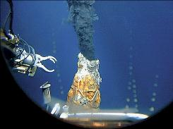 This 1997 photo released by Woods Hole Oceanographic Institution shows the robotic arm of an unmanned aquatic vehicle reaching toward a hydrothermal vent in the east Pacific Ocean far off the coast of Chile. New technology and worldwide demand for metals have combined to make feasible deep ocean mining of the mineral-laden liquid spewed from these vents.
