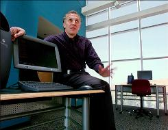 In this 1999 file photo, Rick Belluzo, who was then Silicon Graphics' Chairman and Chief Executive, shows off the company's products.