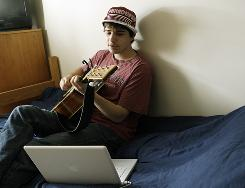 "Mike Nourie, 20, plays guitar and sings in his dorm room at Emerson College in Boston Friday, April 3, 2009. Nourie says he feels a little relieved to escape social networking when he works summers at an inn on Cape Cod, where connection to the wired world is spotty. ""It gives me a chance to relax and focus on other things like music, work and friends,"" he says of his built-in excuse to stay offline."