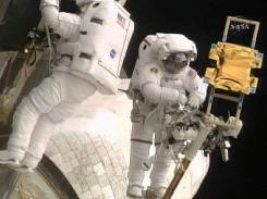 Astronauts Andrew Feustel, left, and John Grunsfeld, on Atlantis' robot arm, work on the Hubble Space Telescope.