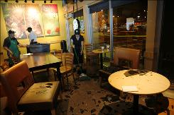 Following an earthquake in the South Bay of the Los Angeles area, Sunday May 17, 1009, employees at a Starbucks in Torrance, Calif.,  clean up  glass that shattered on the floor.