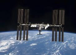The International Space Station is seen with its full complement of solar arrays from the Space Shuttle Discovery.