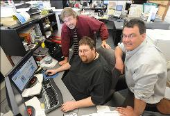 In this photo taken May 13, 2009, Idaho Falls Post Register Publisher Roger Plothow, left, Web Designer Aaron Avery, seated, and Assistant Managing Editor Rob Thornberry  right, are seen in the newsroom in Idaho Falls, Idaho. Plothow has never understood the premise that information needs to be free on the Internet, not when he is paying a 30-person staff to gather the news in eastern Idaho and selling a printed version of the same content that is available online.