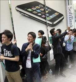 In this July 11, 2008 file photo, customers waiting in line to buy the iPhone 3G celebrate as sales begin in Tokyo.