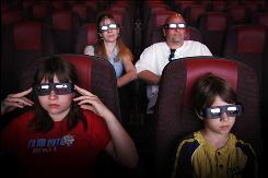 Ashley Burdi, front left, her brother Isaac, front right, and parents Sarah, back left, and Louis, watch the 3-D movie Monsters and Aliens at the Cinemagic movie complex, Friday, May 22, 2009, in Saco, Maine. While movie studios have new and improved 3-D film-making technology, many movie-goers are frustrated to find that the vast majority of movie theaters don't yet have the ability to show 3-D movies.