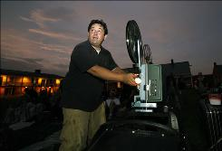 John Young, creator of West Chester Guerilla Drive-In, prepares the film projector inside Fort Mifflin in Philadelphia on Friday May 29, 2009.  For the last four years or so, the 38-year-old Web developer has been showing 16mm films from a 1970s school projector mounted on the sidecar of his 1977 BMW motorcycle. He's presented more than a dozen movies at locations suited for the theme: &quot;Meatballs&quot; at a canoe rental center, &quot;Caddyshack&quot; on a golf course, and most recently, &quot;Ghostbusters&quot; at Fort Mifflin, a favorite haunt of paranormal investigators.