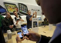 From left, Usher Lieberman of San Jose, Ryan Melcher of Santa Cruz, Calif., and Max Manicini of San Jose, look over the new video features of the new Apple iPhone 3G S as Chuck Dietrich, right, of Salesforce.com compares his old iPhone to the new one at the Apple store in San Francisco.