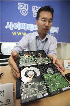 Kim Jae-pil, a police officer of the Cyber Terror Response Center under the National Police Agency, shows seized hard disks which were used for hacking at the agency's headquarters in Seoul, South Korea, Thursday, July 9, 2009.