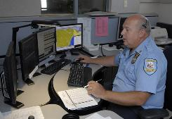 Senior dispatcher Ken Marks works at the Albany Police Department call center. Callers using cellphones have proved problematic for 911 services.
