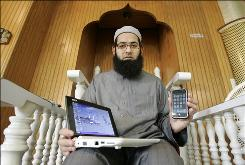 Imam Tahir Anwar poses for a photo at his mosque in San Jose, Calif. with the laptop and iPhone the travels with on Thursday, Nov. 20, 2008. Anwar has traveled abroad 12 times over the past two and a half years and he has been detained upon returning to the U.S. every time. Border agents have searched his laptop and once even took away his cell phone for 15 minutes.