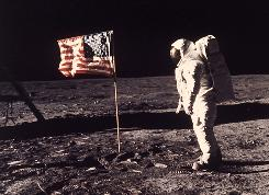 "This July 20, 1969, file photo shows astronaut Edwin ""Buzz"" Aldrin Jr. standing beside the U.S. flag deployed on the moon during the Apollo 11 mission."